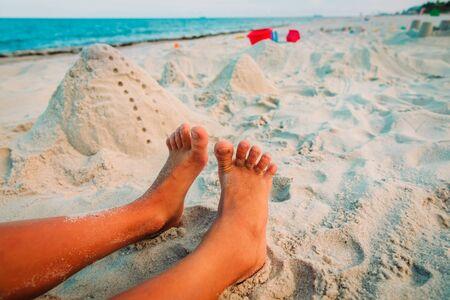 feet of boy play with sand on beach and toys on beach