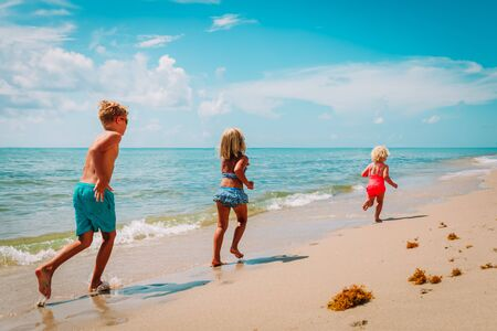 happy kids- boy and girls- run play at beach