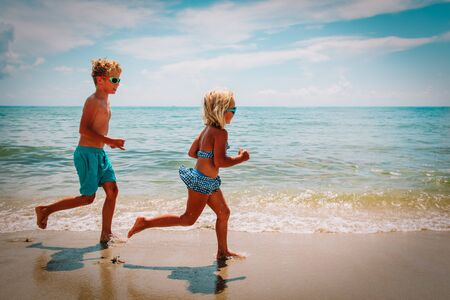 happy little girl and boy running at beach Imagens