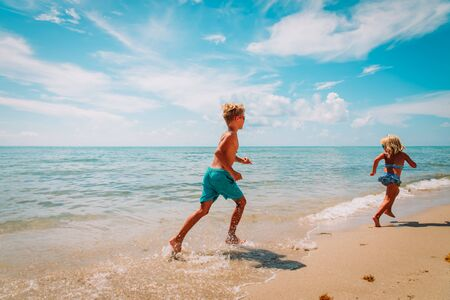happy boy and girl running at beach, kids play with water at sea Imagens