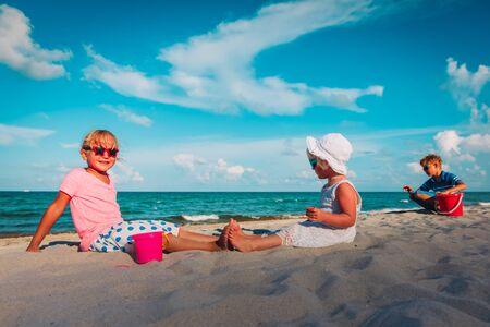 cute kids -girls and boy- play with sand on beach