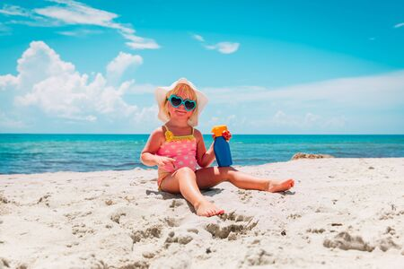 sun protection - little girl with suncream at beach