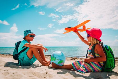 kids travel on beach, boy and girl with globe and toy plane