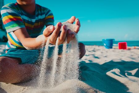boy play with sand on beach vacation, kids summer fun at sea Imagens