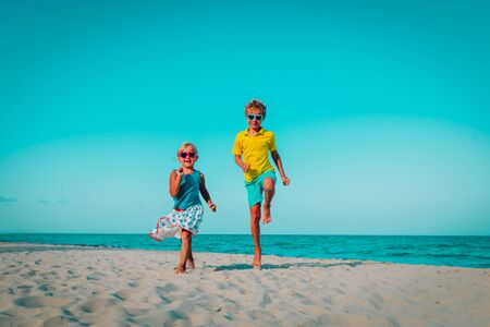 happy cute boy and girl running on beach, kids play at sea