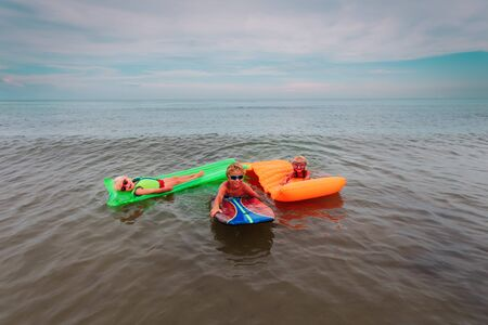happy kids -boy and girls-swim on floaties on beach