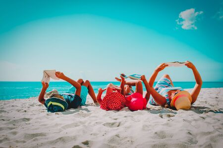 family with kids reading books at beach
