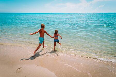 happy boy and girl run to swim on beach