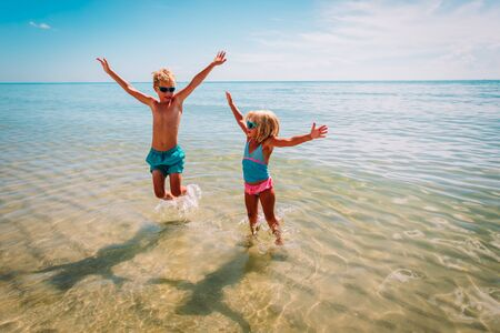happy kids- girl and boy- play with waves on beach Imagens