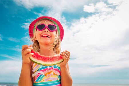 happy cute little girl eating watermelon at beach