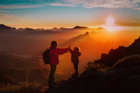 mother with little daughter enjoy travel in sunset mountains Standard-Bild - 129191785