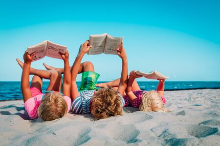 kids -boy and girls- reading books at beach vacation