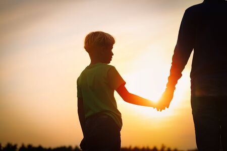 silhouette of father and son holding hands at sunset Imagens
