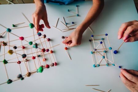teacher and child making geometric shapes from sticks and play dough Imagens