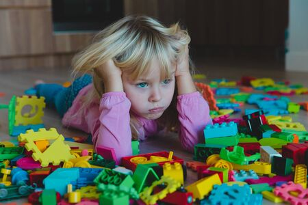 sad little girl, stress, exhaustion with toys scattered around