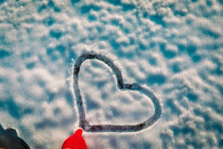 drawing heart on snow, love winter concept