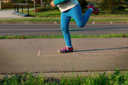 little girl playing hopscotch in the city