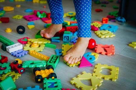 too much toys at home- girl steps on toys trying to go through Stock fotó