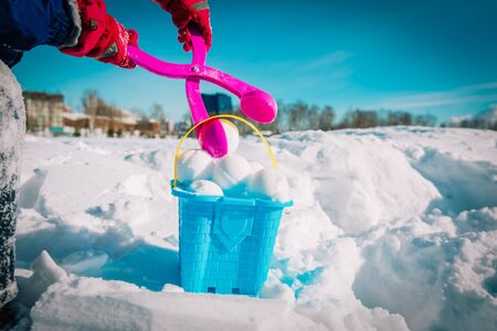 child making snowballs in winter nature, kids play outdoors Zdjęcie Seryjne