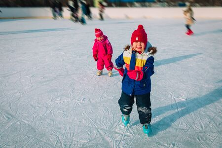 little girls learning to skate together in snow, kids winter sport