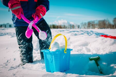 child making snowballs in winter nature, kids play outdoors Stock fotó