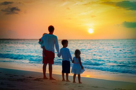 father with three kids walking on beach at sunset