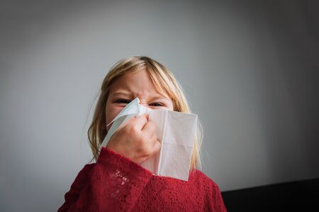 little girl wiping and blowing nose, infection or allergy