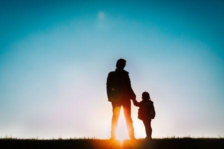 Vater mit kleiner Tochter spazieren bei Sonnenuntergang Standard-Bild