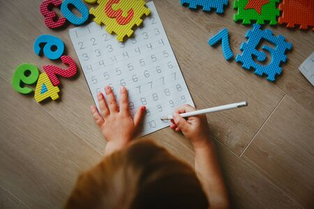 little girl learning write and culculate numbers