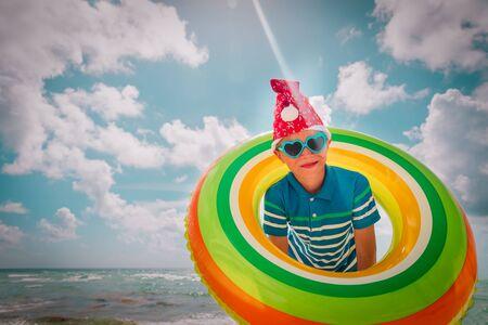 happy cute boy celebrating christmas on tropical beach