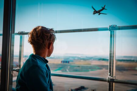 boy waiting in airport looking at planes, family travel