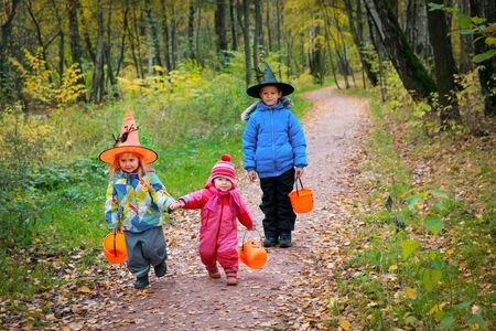kids celebrating halloween, boy and girls trick or treating in autumn
