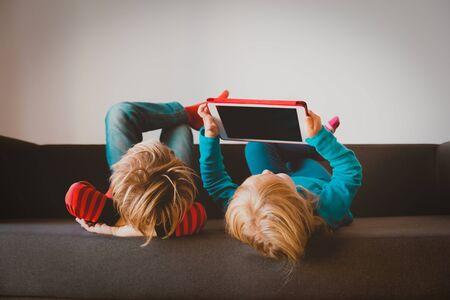 kleiner Junge und Mädchen, die zu Hause auf das Touchpad schauen
