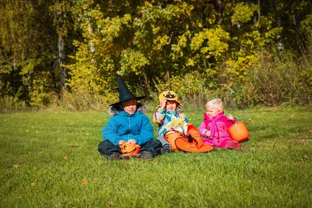 kids in halloween costume play in nature, trick or treating