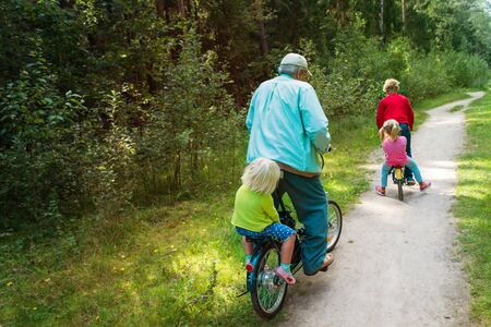 active senior granddad with kids riding bikes in nature Imagens