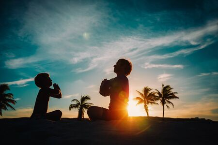 father and son doing yoga at sunset
