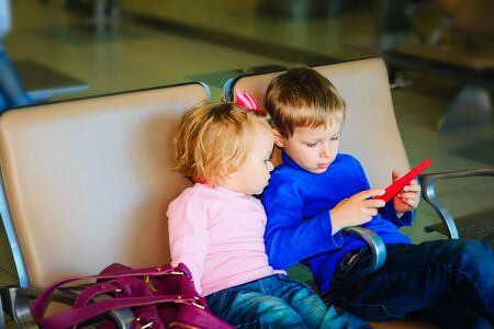 boy and girl looking at touch pad while travel in the airport