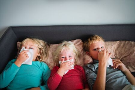 kids wiping and blowing nose in bed, infection or allergy