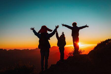gelukkig gezin met kinderen reizen in de bergen bij zonsondergang, silhouet van familie geniet van wandelen Stockfoto