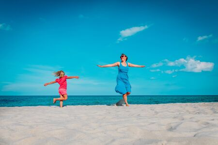 happy mother with little daughter play on beach