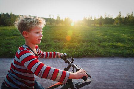 happy cute boy enjoy riding bike in sunset nature