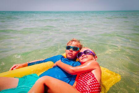 happy kids, boy and girl, swim on floatie on beach vacation