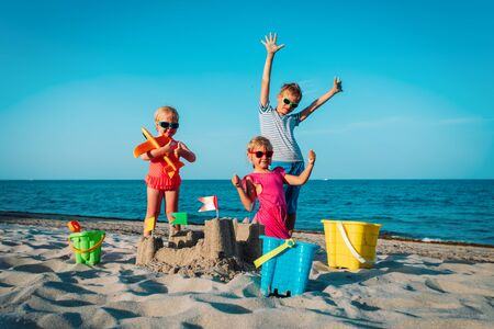 happy kids -boy and girls- play with sand on beach Imagens