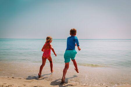happy boy and girl run swim on beach vacation
