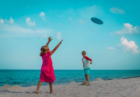boy and girl playing with flying disc at beach