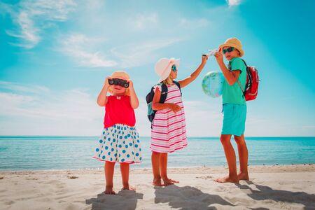 kids travel on beach, boy and girls with globe, toy plane and binoculars