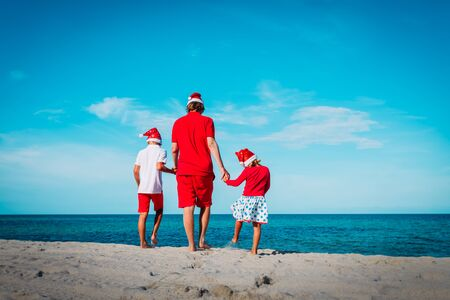 father with kids walk on tropical beach at Christmas