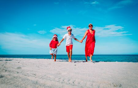 happy family- mom, son and daughter- celebrating Christmas on beach Stok Fotoğraf