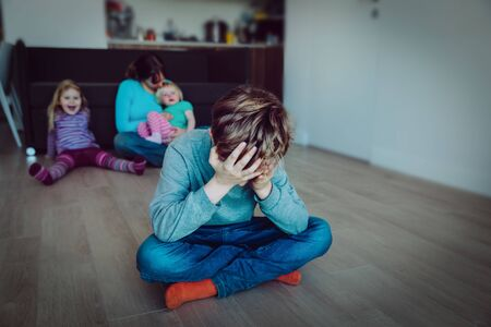 rivalité familiale pleurant enfant triste, soeur souriante et mère tenant un autre enfant