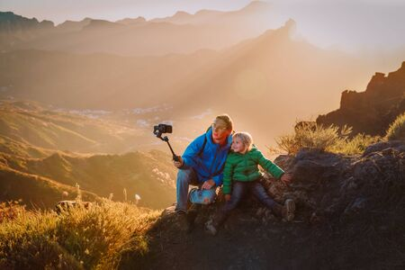 father with little daughter making selfie in mountains, family travel